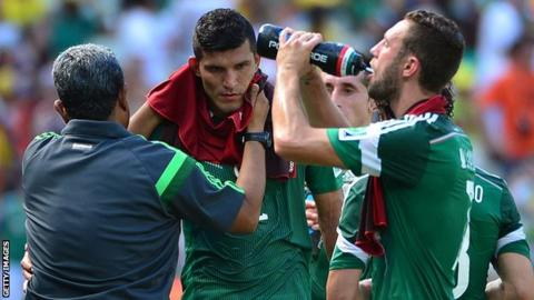 Mexico players have a drinks break during the 2014 World Cup