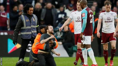 One of the fans who came on to the pitch during West Ham's defeat by Burnley is grabbed by a steward