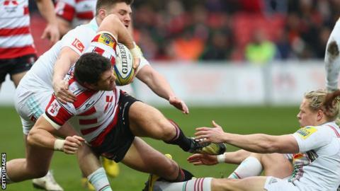 James Hook get through two tackles on the way to scoring Gloucester's opening try