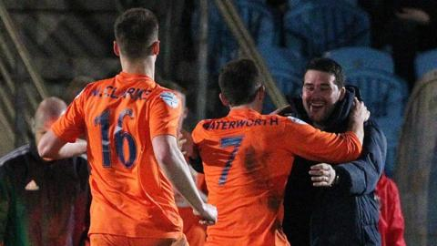 Matthew Clarke and Andrew Waterworth run to celebrate with Linfield manager David Healy as Linfield take the lead against Ballymena