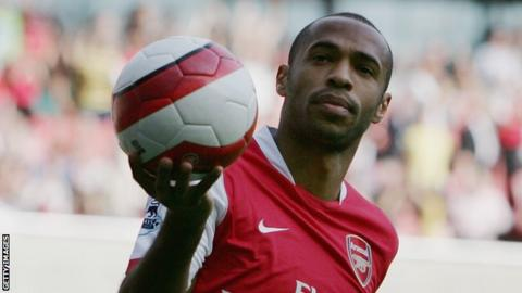 Arsenal striker Thierry Henry holds up the ball in celebration after scoring a goal in a Premier League match