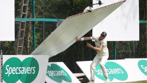 Gloucestershire bowler David Payne had to avoid a falling sight screen at Spytty Park