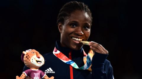 British boxer Caroline Dubois bites her gold medal after winning the lightweight title at the Youth Olympic Games in Buenos Aires