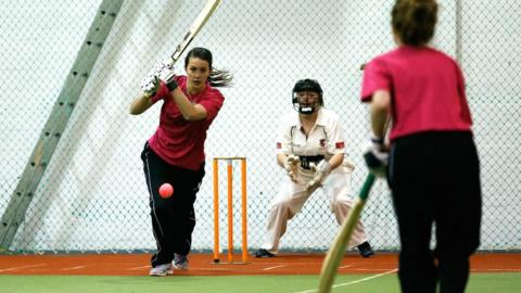Women's playing cricket indoors