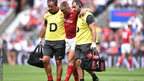 Gareth Anscombe being helped off at Twickenham