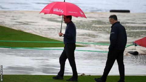 Umpires inspect a waterlogged pitch at Taunton
