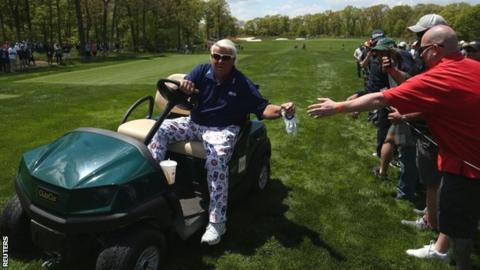 John Daly driving a golf buggy at Bethpage Black