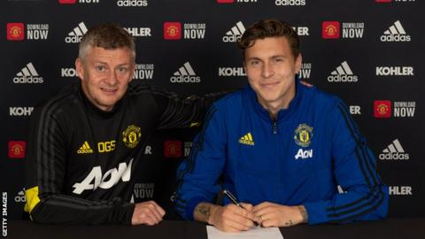 Victor Lindelof signing his new contract alongside Ole Gunnar Solskjaer.