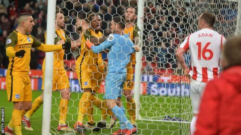 Charlie Adam looks on in dismay as Brighton goalkeeper Mat Ryan is congratulated by his team-mates for saving the Stoke midfielder's late spot-kick