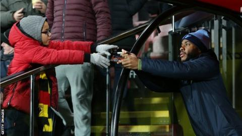 Raheem Sterling of Manchester City signs an autograph for a fan during the Premier League match between Watford FC and Manchester City at Vicarage Road on December 4, 2018 in Watford, United Kingdom