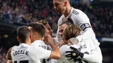 Real Madrid players celebrate the opening goal against Valencia