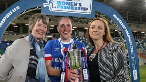 Vicky Davies of Danske Bank and Maura Muldoon from the Women's Premiership Committee present Linfield Ladies captain Sarah Venney with the Premiership trophy before their final match of the season against Mid-Ulster at Windsor Park