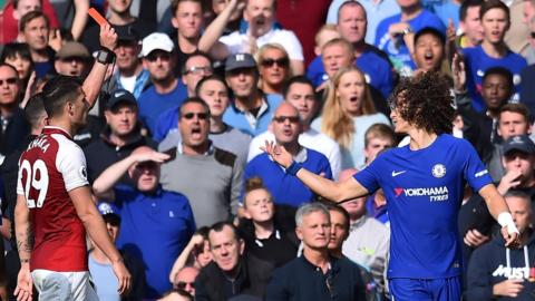 Chelsea's David Luiz protests to referee Michael Oliver as Granit Xhaka looks on