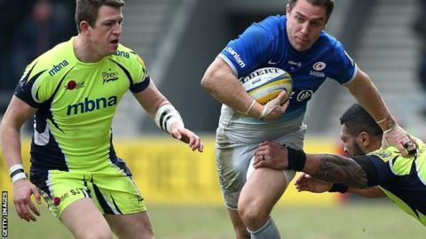 hris Wyles of Saracens breaks through the tackle of Johnny Leota