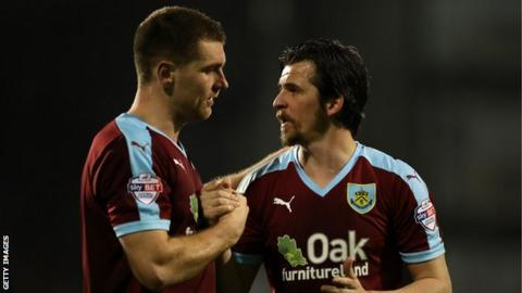 Sam Vokes and Joey Barton embrace while with Burnley
