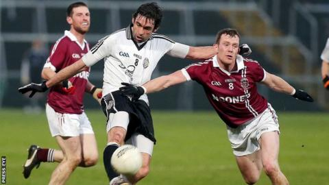 Slaughtneil's Patsy Bradley attempts to block a shot by Omagh's Joe McMahon shot in the 2014 Ulster Club Football Final