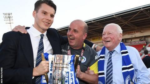 David Sharpe, Paul Cook and David Whelan celebrate Wigan winning League One