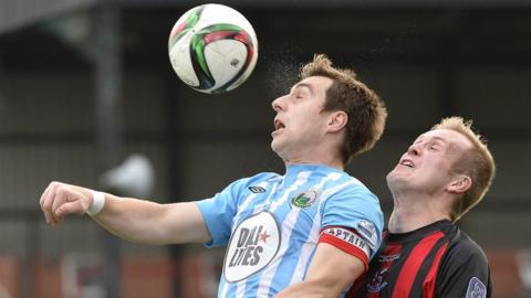 John Boyle of Warrenpoint Town comes under pressure from Crusaders striker Jordan Owens