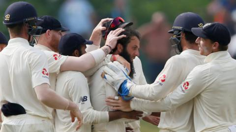 England players mob Moeen Ali after he takes a wicket on day four of the second Test against Sri Lanka