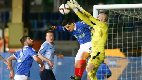 Linfield defender Jimmy Callacher challenges United keeper Alan Blayney for the high ball