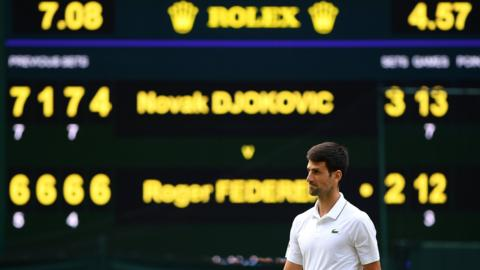 Novak Djokovic in front of the scoreboard showing his winning score over Roger Federer