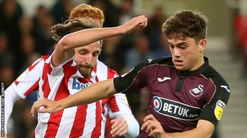Joe Allen (left) challenges Daniel James during a championship match between Stoke City and Swansea City