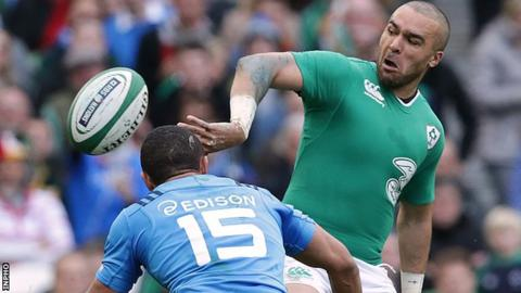 Simon Zebo produces an off-load as he is tackled by Italy full-back David Odiete