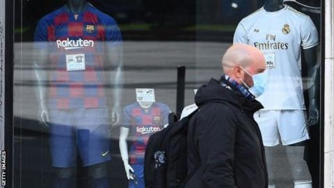 Man in mask walks past Barcelona and Real Madrid football shirts on sale