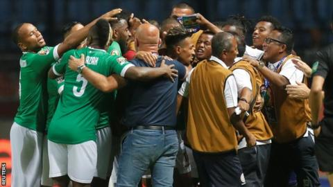 Madagascar players celebrate with the coaching staff as they score their first Africa Cup of Nations goal