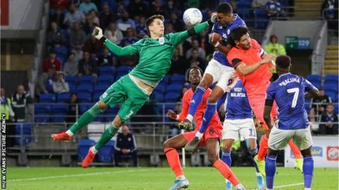 Cardiff City's Robert Glatzel heads towards goal under the challenge of Huddersfield Town goalkeeper Kamil Grabara