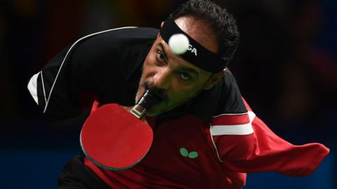 Ibrahim Hamadtou of Egypt plays table tennis, holding the bat with his mouth