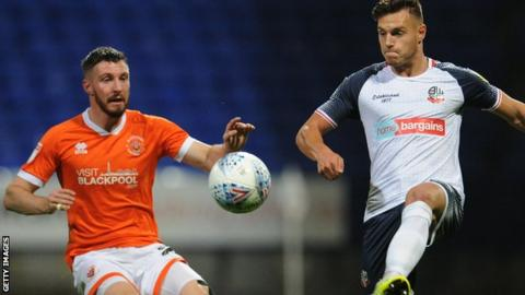 Bolton Wanderers' Dennis Politic (right) comes under pressure from Blackpool's James Husband