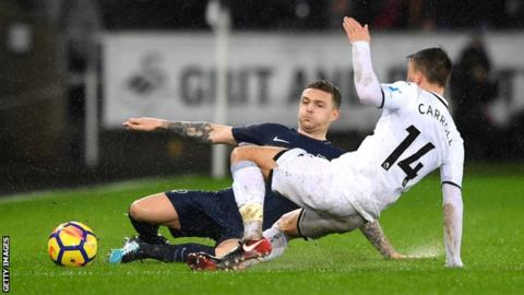Kieran Trippier of Tottenham Hotspur is challenged by Swansea City's Tom Carroll on the rain-drenched Liberty Stadium pitch