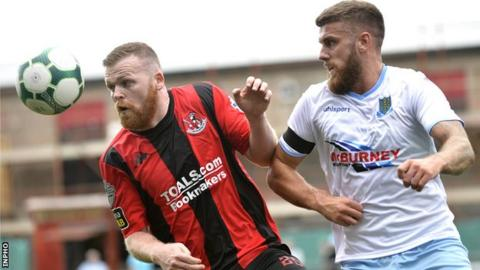 Battle of the beards! Crusaders' Ross Clarke and United defender Steven McCullough contest a high ball