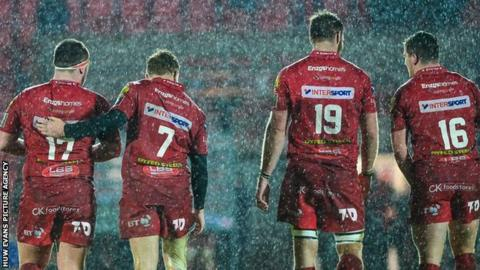 Scarlets players take a wet lap of honour in torrential rain after beating Ospreys on Boxing Day