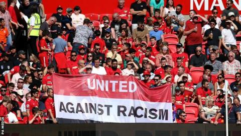 Manchester United fans with an anti-racism banner