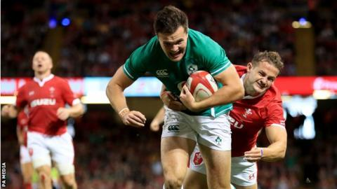 Rugby Ireland wing Jacob Stockdale beats Wales' Hallam Amos to score