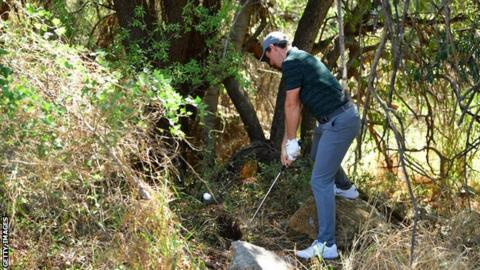 Rory McIlroy attempts an escape from the trees on the second hole on Saturday