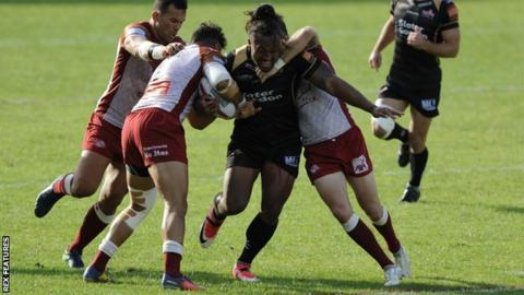 Atalea Vea trying to bust through a tackle against Catalans