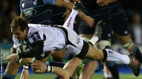 Tom Grabham of Ospreys is tackled by Rhodri Davies of Cardiff Blues