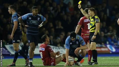 Referee Lloyd Linton shows Aaron Shingler a yellow card