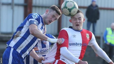 Coleraine Stephen O'Connell challenges Linfield forward Michael O'Connor