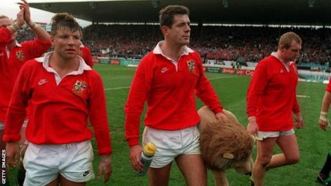Gavin Hastings, carrying a Lions mascot, and flanked by Rob Andrew (left) and Dean Richards (right), walks off the pitch after the Lions' third Test defeat against New Zealand in 1993