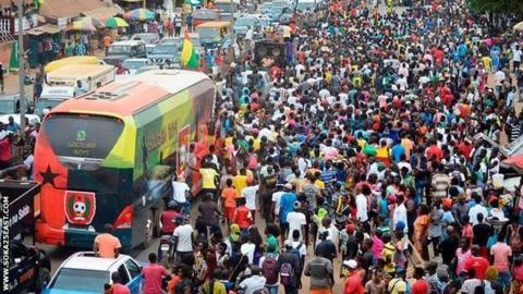Guinea-Bissau's team coach travels through the crowds