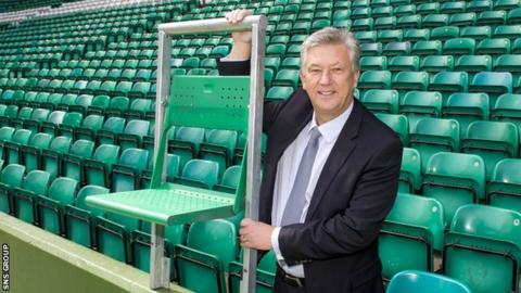 Celtic chief executive Peter Lawwell shows off the rail seat technology