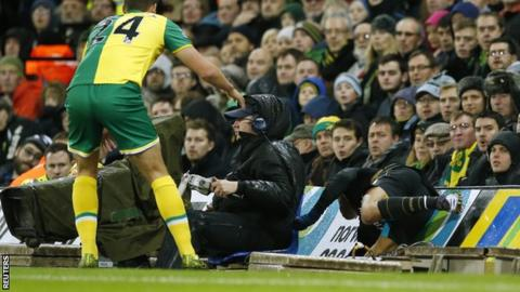 Alexis Sanchez (right) falls into the barriers at Norwich