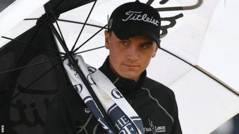 Young Scottish amateur Sam Locke shelters from the rain at a wet Carnoustie
