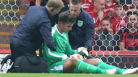 Nick Pope receives treatment after being injured against Aberdeen