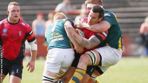 Chris Davies of Aberavon is tackled by Osian Davies and Craig Locke of Merthyr