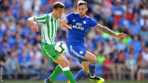 Sergio Canales of Real Betis holds off Joe Ralls of Cardiff City during the Pre-Season Friendly match between Cardiff City and Real Betis at Cardiff City Stadium